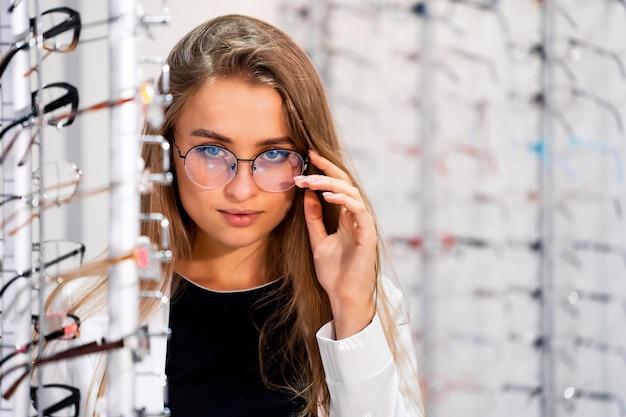 Klientka Lub Optyk Stoi Z Surowymi Okularami W Sklepie Optycznym Premium Zdjęcia
