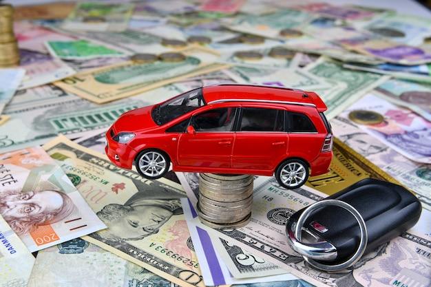 Kluczyk i czerwony samochodzik na wieży z monet. różnych walut narodowych i jednego symbolicznego banknotu złotego dolara. kosztów zakupu, wynajmu i utrzymania samochodu. Premium Zdjęcia