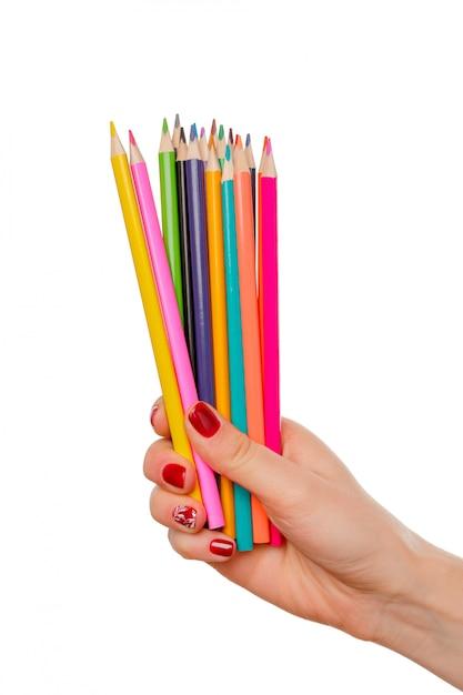 Kobieca ręka trzyma kolorowy ołówek (kolorowy) jak tęcza na białym biurku Premium Zdjęcia