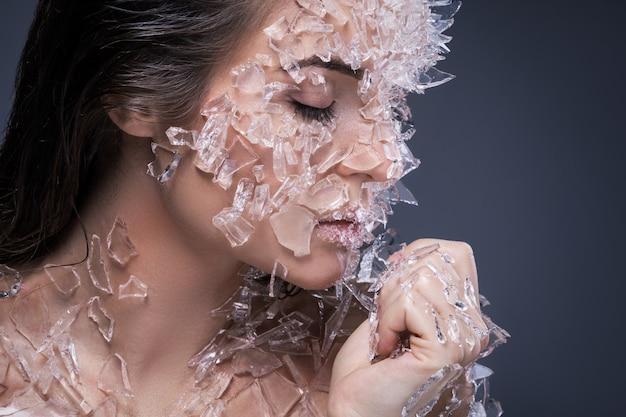 Kobieca Twarz Pokryta Dużą Ilością Małych Kawałków Szkła Premium Zdjęcia