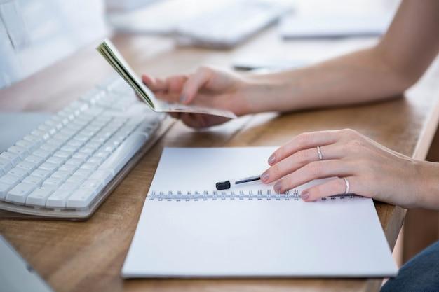 Kobiece dłonie spoczywające na biurku trzyma długopis i paszport Premium Zdjęcia