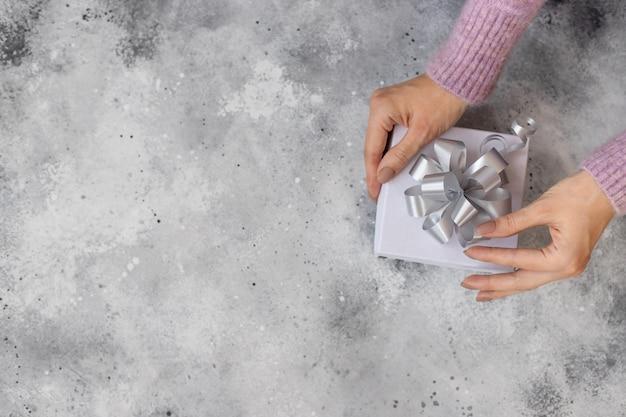 Kobiece Dłonie Trzymające świąteczne Pudełko Ze Srebrną Kokardką. Piękny Nagi Manicure Na Rękach. światło Betonowe Tło, Widok Z Góry, Miejsce Premium Zdjęcia