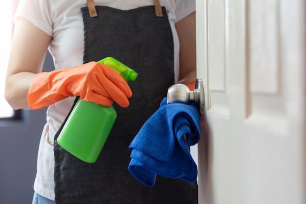 Kobiece Dłonie W Pomarańczowych Gumowych Rękawiczkach Czyszczących Dotykającą Powierzchnię Drzwi, Klamkę Z Niebieską ściereczką Z Mikrofibry I Zieloną Antybakteryjną Butelkę W Sprayu. Premium Zdjęcia