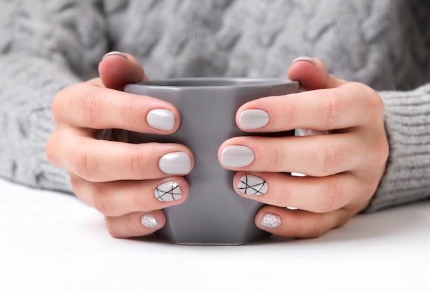 Kobiece dłonie z geometrycznym wzorem do paznokci w przytulnym swetrze Premium Zdjęcia