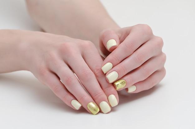 Kobiece Dłonie Z Manicure, żółte Ze Złotym Pokryciem Paznokci. Premium Zdjęcia