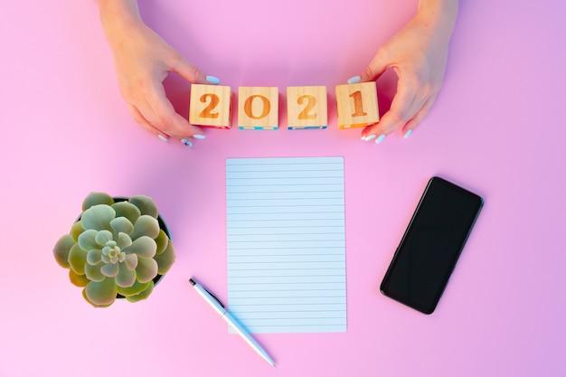 Kobiece Ręce I Otwarty Notatnik Na Różowym Tle Premium Zdjęcia