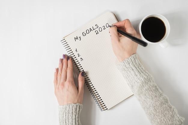 Kobiece Ręce Pisząc Moje Cele 2020 W Zeszycie. Kubek Kawy Na Stole, Widok Z Góry Premium Zdjęcia
