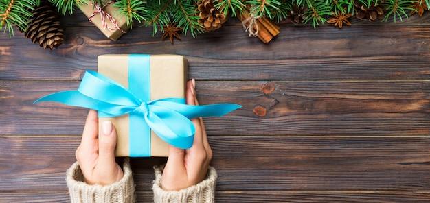 Kobiece ręce trzyma ręcznie prezent pudełko w papierze z recyklingu na ciemnym drewnianym stole, koncepcja przygotowania świątecznego, transparent opakowanie prezentów Premium Zdjęcia