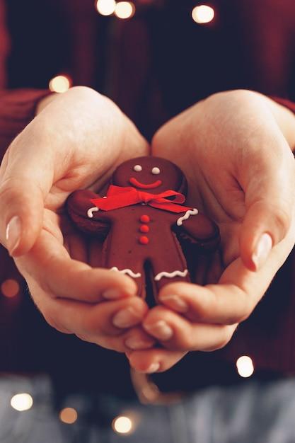 Kobiece Ręce, Trzymając Człowieka Z Piernika Z Bliska, Koncepcja Boże Narodzenie Premium Zdjęcia
