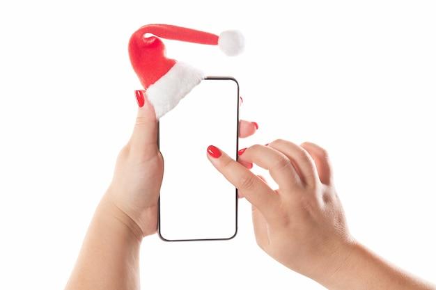 Kobiece Ręce Trzymając Inteligentny Telefon Komórkowy Z Santa Hat Premium Zdjęcia