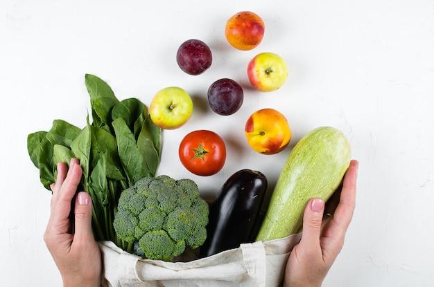 Kobiece Ręce Trzymając Warzywa Wegańskie, Torba Wielokrotnego Użytku Cotoon Na Jasnym Stole. Zero Odpadów, Koncepcja Opieki Premium Zdjęcia