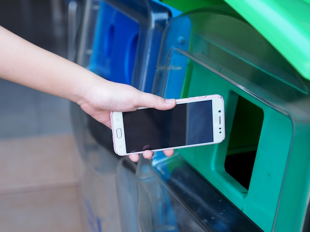 Kobiece Ręce Wrzucają Stary Telefon Do Kosza. Premium Zdjęcia
