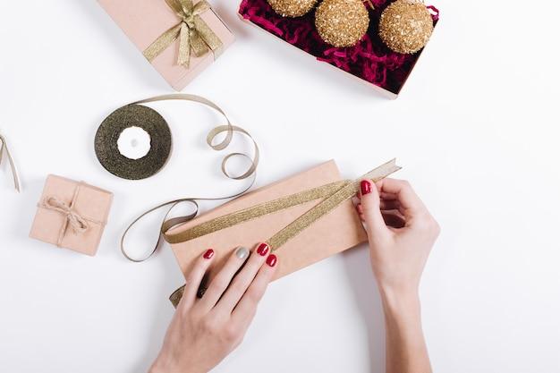 Kobiece Ręce Z Czerwonym Manicure Pakują Prezenty W Pudełka I Wiążą Je Wstążkami Premium Zdjęcia