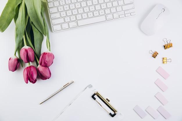 Kobiecy Obszar Roboczy Biurka Z Tulipanami, Klawiaturą Komputerową, Złotymi Klipami Na Białym Tle Premium Zdjęcia