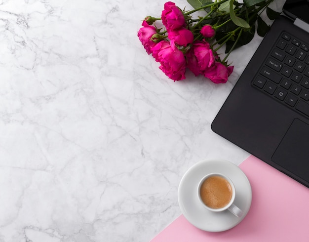 Kobiecy obszar roboczy z laptopem, bukiet róż i kawa na marmurowym stole. Premium Zdjęcia