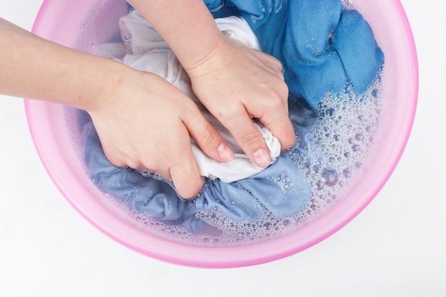 Kobiet Ręki Myje Biel I Błękitów Ubrania Z Pianą W Basenie, Odgórny Widok Premium Zdjęcia