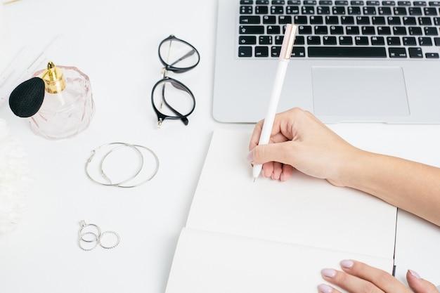 Kobiet ręki robi notatkom w notepad na białym stole z laptop klawiaturą Premium Zdjęcia