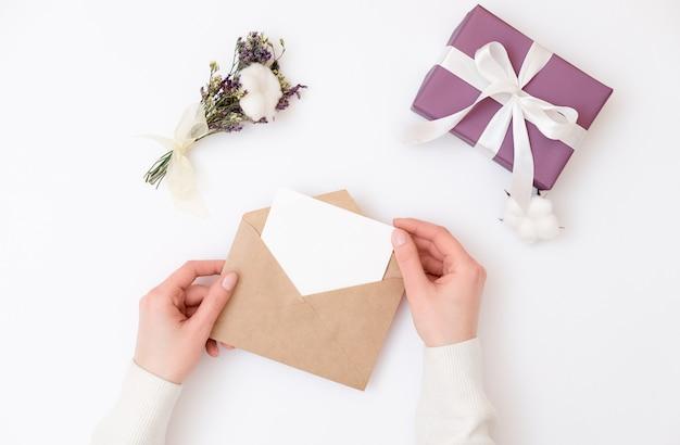 Kobiet ręki trzyma kraft kopertę z pustą ślubną zaproszenie kartą Premium Zdjęcia