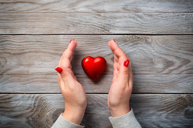 Kobiet Ręki Z Czerwonymi Gwoździami I Dekoracyjny Serce Na Drewnianym Tle. Premium Zdjęcia