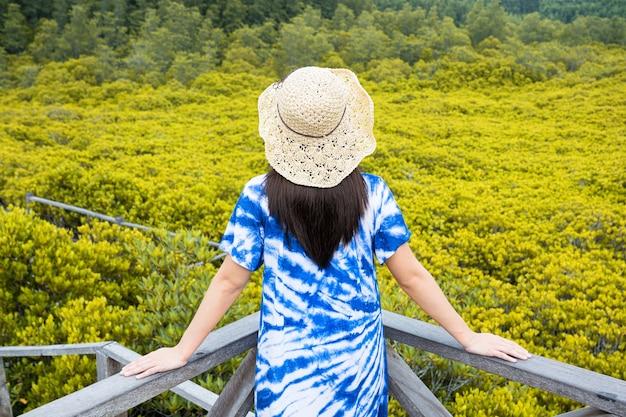 Kobieta Azjatyckich Turystycznych Stojących Na Promenadzie Lasu Namorzynowego Tung Prong, Tajlandia. Premium Zdjęcia