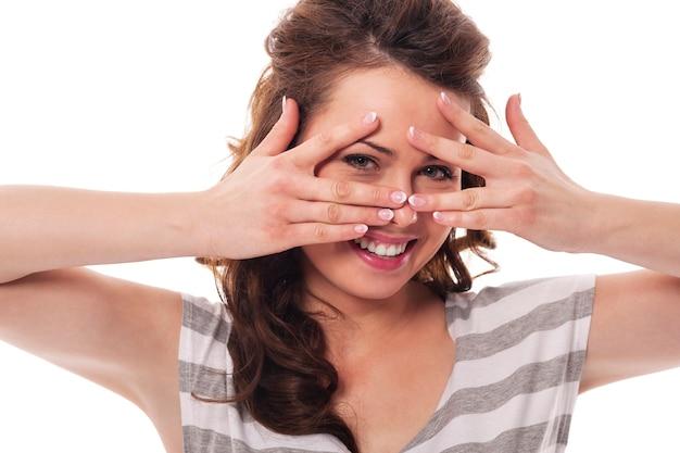 Kobieta Bawi Się Chowając Się Za Palcami Darmowe Zdjęcia