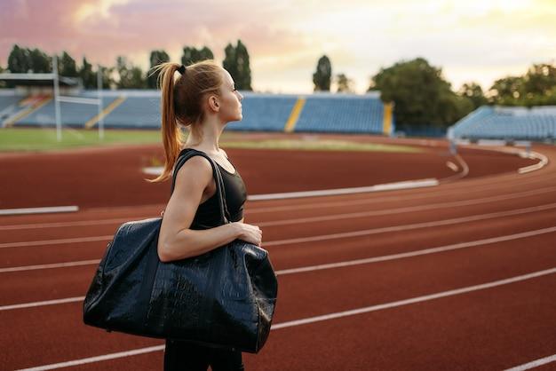Kobieta Biegacz Trzyma Torbę Sportową, Trening Na Stadionie Premium Zdjęcia