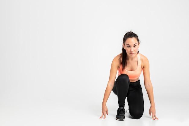 Kobieta biegacz w pozycji początkowej z miejsca na kopię Darmowe Zdjęcia