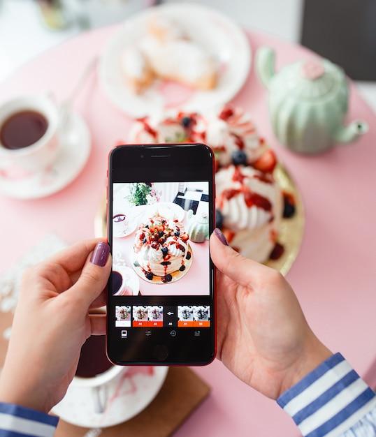 Kobieta Bierze Fotografię Ciasto Z Jagodami Na Smartphone Darmowe Zdjęcia
