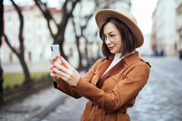 Kobieta Bierze Fotografię Na Jej Telefonie W Jesień Dniu Outside Darmowe Zdjęcia