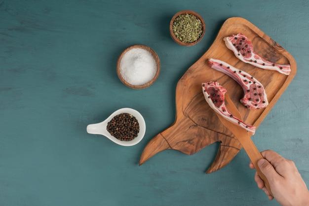 Kobieta Bierze Kawałek Surowego Mięsa Z Drewnianej Deski. Darmowe Zdjęcia