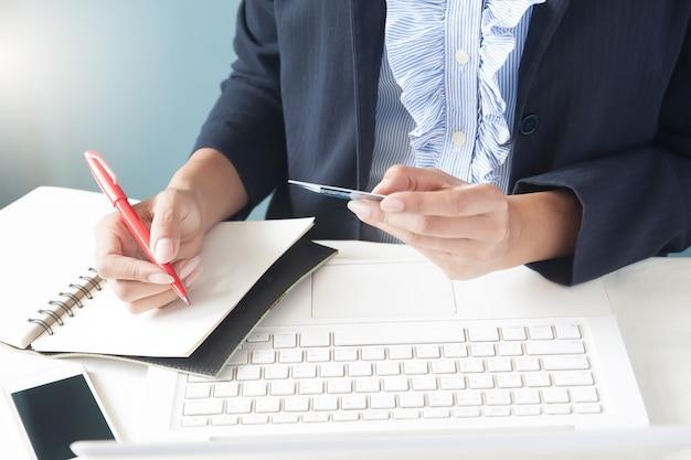 Kobieta biznesowych w ciemnym kolorze posiadania karty kredytowej, przy użyciu komputera przenośnego i pisanie na notebooka, koncepcji biznesowych i zakupów online Darmowe Zdjęcia