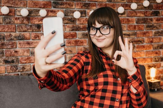 Kobieta Blogerka Przesyłająca Strumieniowo Online Za Pomocą Smartfona I Dająca Znak Ok Darmowe Zdjęcia