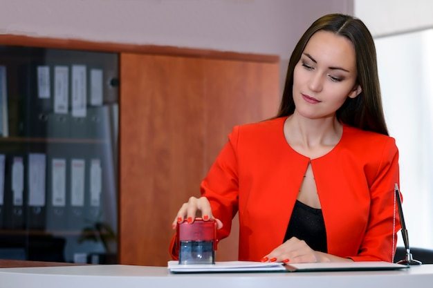 Kobieta Boss W Jaskrawoczerwonym Garniturze Pieczętuje Umowę W Recepcji. Premium Zdjęcia