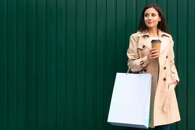 Kobieta Buźka Na Zewnątrz Kawę I Trzymając Torby Na Zakupy Premium Zdjęcia