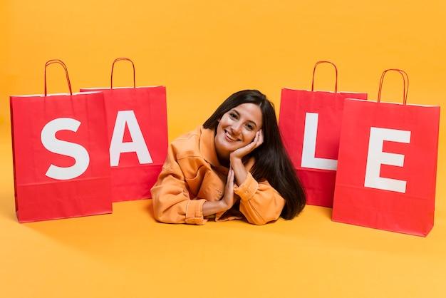 Kobieta Buźka Pozuje Między Torby Na Zakupy Sprzedaży Darmowe Zdjęcia
