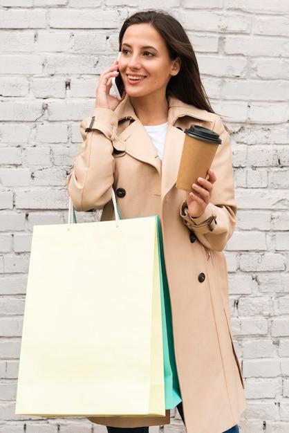 Kobieta Buźka Rozmawia Przez Telefon Na Zewnątrz, Trzymając Filiżankę Kawy I Torby Na Zakupy Darmowe Zdjęcia