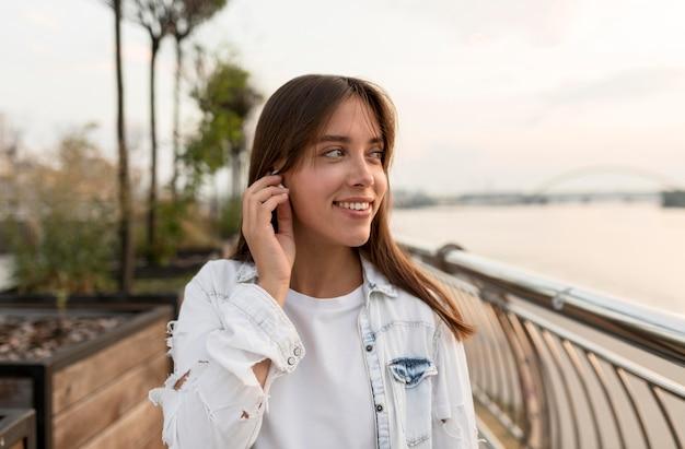 Kobieta Buźka Zakładanie Słuchawek, Podczas Gdy Na Zewnątrz Darmowe Zdjęcia