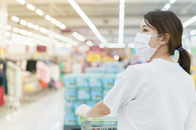 Kobieta Chroni Się Przed Infekcją Maską Chirurgiczną I Rękawiczkami, Z Koszykiem Na Zakupy W Supermarkecie Po Pandemii Koronawirusa. Premium Zdjęcia