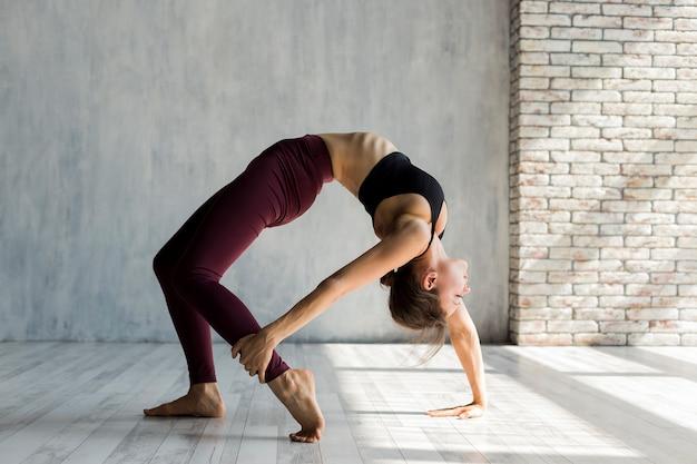 Kobieta chwyta jej stopę podczas gdy stojący w bridżowej joga pozie Darmowe Zdjęcia