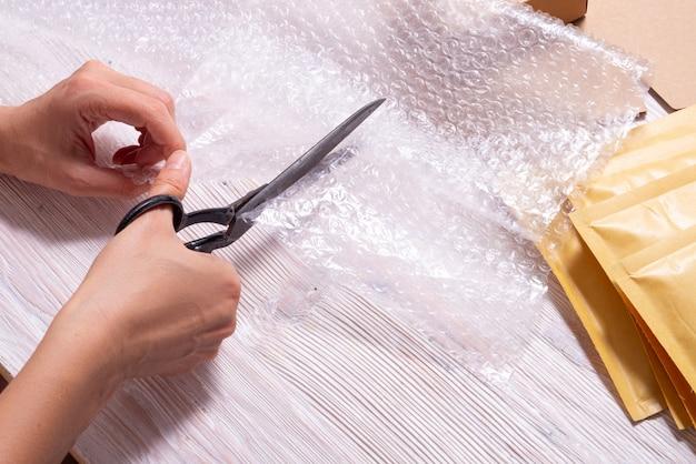 Kobieta Cięcia Folii Bąbelkowej Nożyczkami Premium Zdjęcia