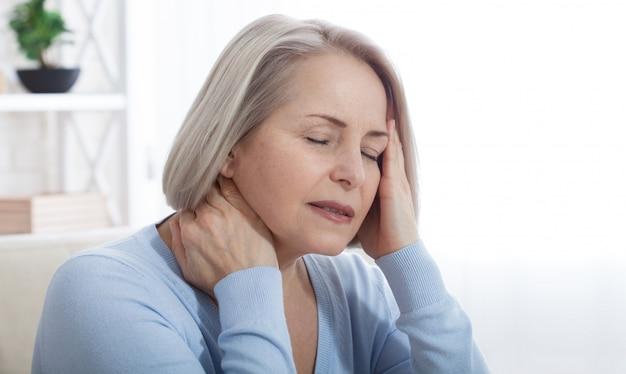 Kobieta Cierpiąca Na Stres Lub Ból Głowy Wykrzywiony Bólem, Gdy Trzyma Kark Premium Zdjęcia