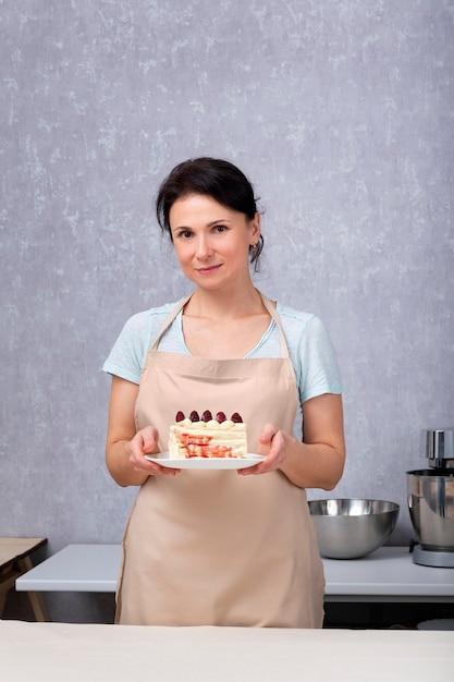 Kobieta Cukiernik Trzyma Ciasto Z Jagodami. Premium Zdjęcia