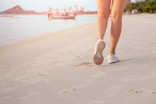 Kobieta ćwiczenia spacery na plaży w godzinach porannych. Premium Zdjęcia