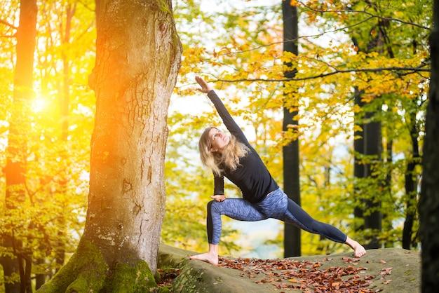 Kobieta ćwiczy joga w jesień lesie na dużym kamieniu Premium Zdjęcia