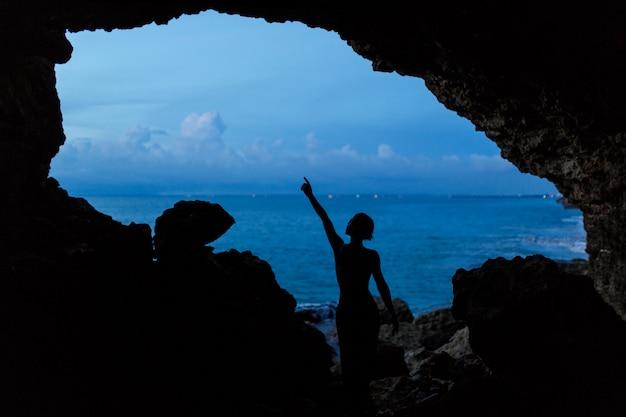 Kobieta czekać zachód słońca w jaskini balinesse na plaży oceanu. Premium Zdjęcia