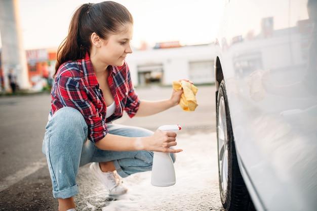 Kobieta Czyści Tarczę Koła Samochodu Sprayem, Myjnią Samochodową. Pani Na Samoobsługowym Myciu Samochodów. Mycie Pojazdów Na Zewnątrz W Letni Dzień Premium Zdjęcia