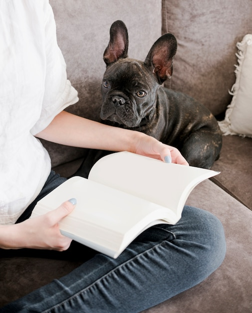 Kobieta Czyta Książkę Z Jej Szczeniakiem Darmowe Zdjęcia