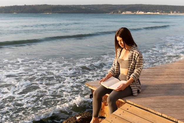 Kobieta Czytająca Książkę Na Plaży Darmowe Zdjęcia