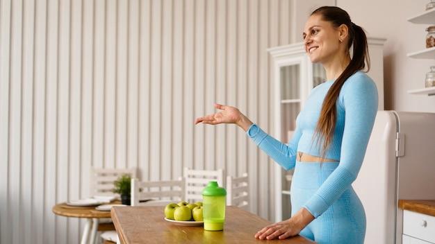 Kobieta Dietetyk Opowiada O Zaletach Zdrowej Diety W Kuchni. Widok Z Boku. Koncepcja Vlogowania Lub Seminarium Zdrowego Stylu życia Premium Zdjęcia