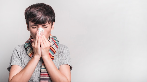Kobieta Dmucha Jej Nos W Papier Tkankowy Przeciw Popielatemu Tłu Z Zamkniętymi Oczami Darmowe Zdjęcia